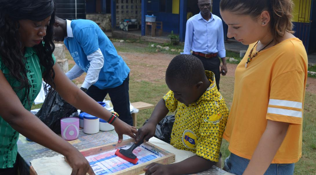 A gap year programs abroad volunteer helps a teacher and child in Ghana with an art project.
